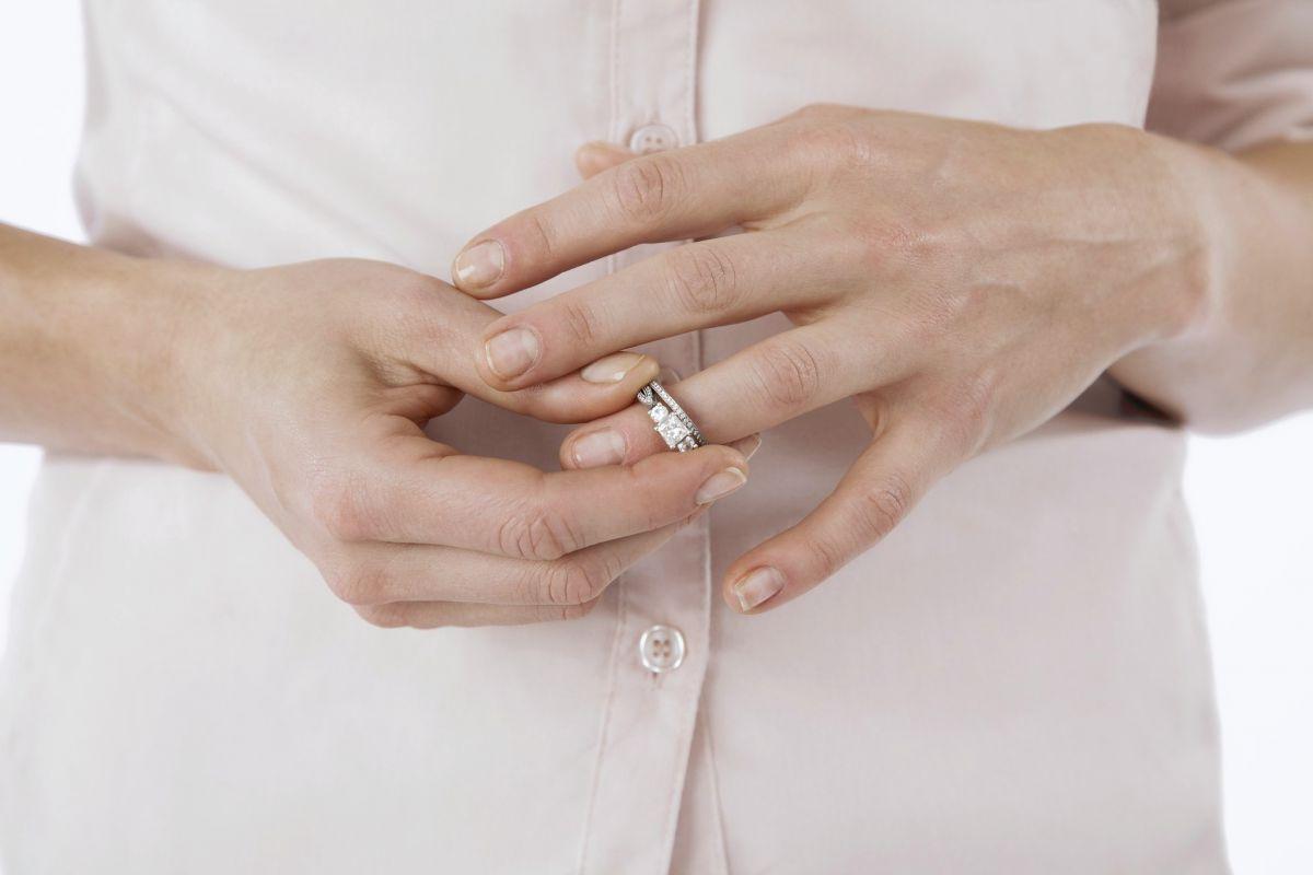 женщина снимает с пальца кольцо